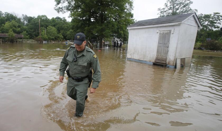 El patrullero estatal de West Virginia C.S. Hartman camina desde un cobertizo que comprobó mientras él y otras personas registran viviendas en Rainelle, West Virginia., el sábado 25 de junio de 2016. (AP Foto/Steve Helber)
