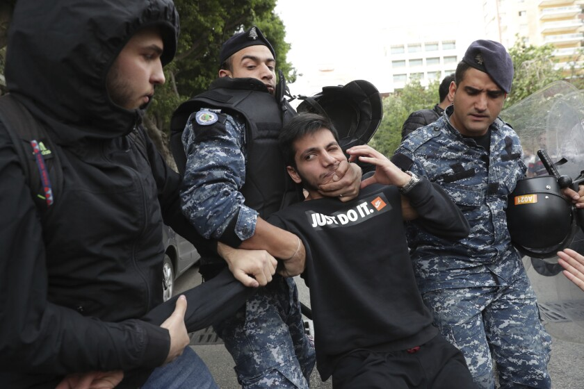 Lebanese riot police scuffle with anti-government protesters blocking a road in Beirut on Nov. 25, 2019.