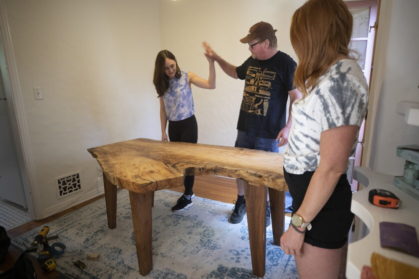 Melissa Anderson high-fives her dad David who custom made a dining table for her new L.A. apartment.