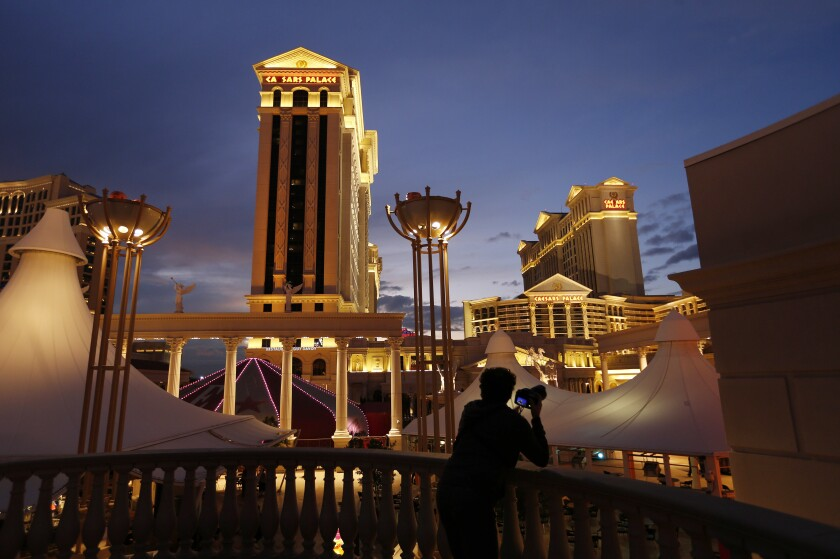 FILE - In this Jan. 12, 2015, file photo, a man takes pictures of Caesars Palace hotel and casino in Las Vegas. A $17.3 billion buyout creating the world's biggest casino company has final regulatory approval. The New Jersey state Casino Control Commission voted Friday, July 17, 2020 to let Nevada-based Eldorado Resorts acquire Caesars Entertainment Corp. (AP Photo/John Locher, File)