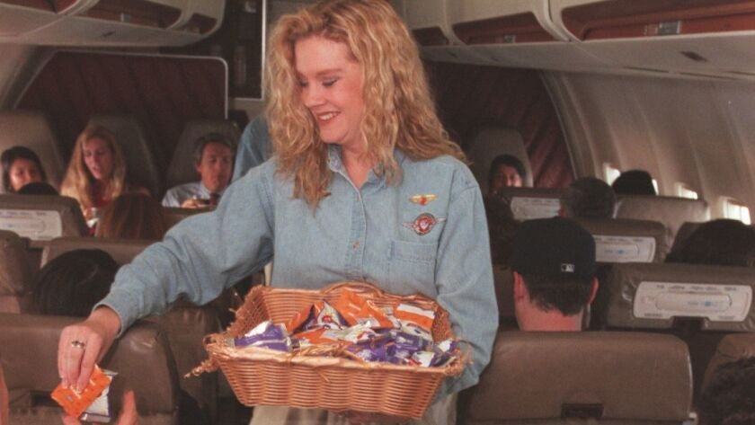 "A Southwest Airlines flight attendant hands out snacks on a 1996 flight from Oakland to Burbank. Although peanuts ""forever will be part of Southwest's history and DNA,"" the airline said, it plans to stop offering them to passengers on Aug. 1."