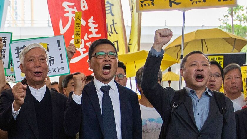 Occupy Central activists, from left, the Rev. Chu Yiu-ming, Chan Kin-man and Benny Tai prepare to enter court at West Kowloon Magistrates Court, Hong Kong, on Tuesday.