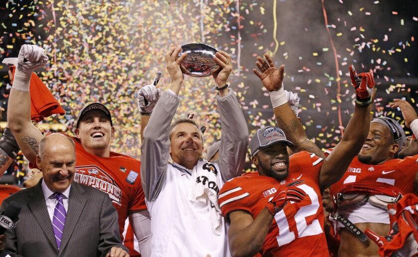 Ohio State Coach Urban Meyer and his team celebrate after a 59-0 win against Wisconsin in the 2014 Big Ten championship game on Dec. 6 at Lucas Oil Stadium.