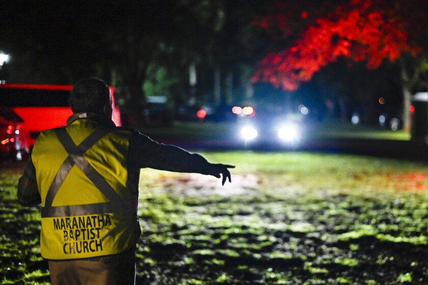 "Mayor L.E. ""Boze"" Godwin III directs cars to parking behind Maranatha Baptist Church in Plains, Ga., before dawn."