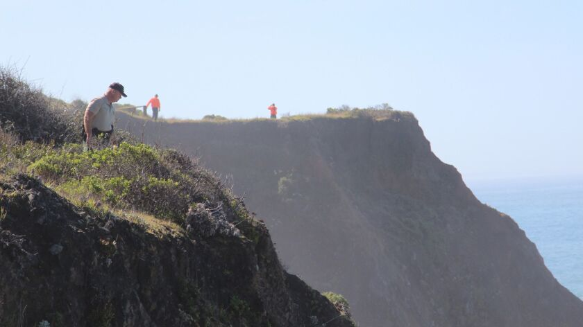 In this photo from March 29, 2018, Deputy Bill Holcomb looks down the cliff near the crash site in Mendocino County as search and rescue volunteers scour the area after a family's SUV plunged into the sea.