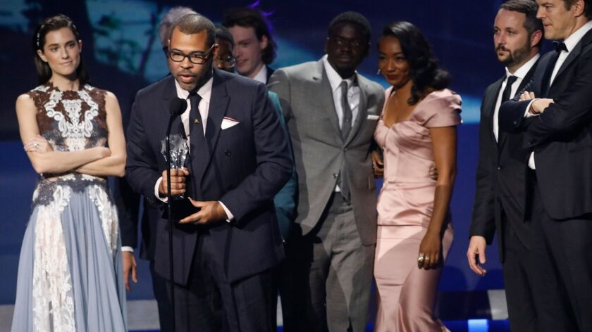 "Jordan Peele gives the acceptance speech after winning the scifi/horror movie award for his film, ""Get Out,"" with members of the cast and crew standing behind him, at the Critics Choice Awards."