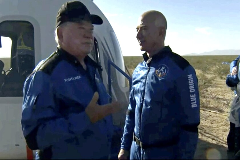 William Shatner talks with Jeff Bezos next to a space capsule