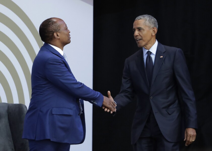 FILE - In this file photo dated Tuesday, July 17, 2018, former US President Barack Obama, right, shakes hands with Patrice Motsepe, as he arrives at the Wanderers Stadium in Johannesburg, South Africa, to deliver the 16th Annual Nelson Mandela Lecture. The election to lead African soccer is seeming to be dominated by FIFA president Gianni Infantino, who supports South African billionaire Patrice Motsepe to win the top job in a ballot next week. (AP Photo/Themba Hadebe, FILE)