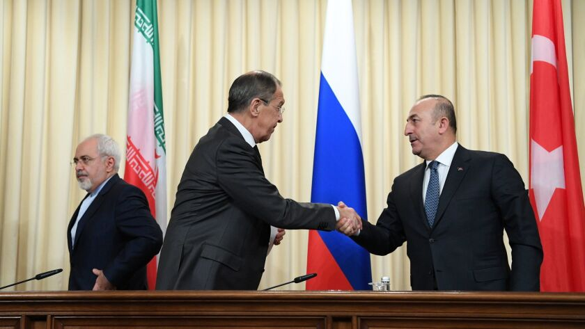Russian Foreign Minister Sergei Lavrov, center, shakes hands with his Turkish counterpart, Mevlut Cavusoglu, after a news conference in Moscow on Tuesday. At left is Iranian Foreign Minister Mohammad Javad Zarif.