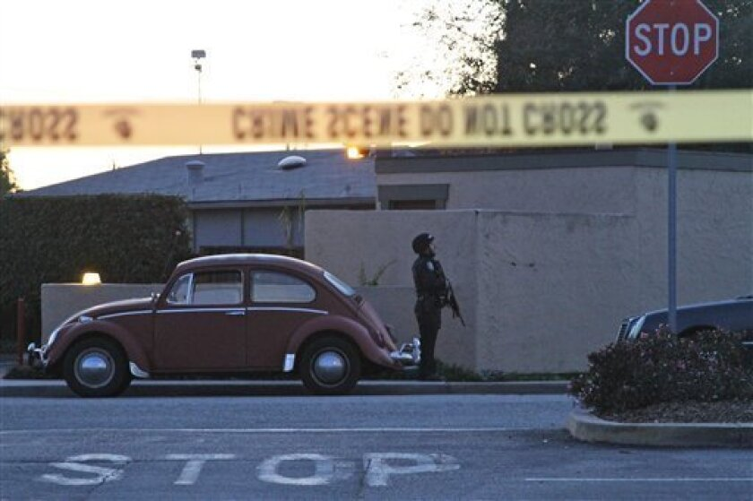 A police officer secures the shooting scene near N. Branciforte Avenue and Doyle Street Tuesday, Feb. 26, 2013 in Santa Cruz, Calif., where two Santa Cruz Police Detectives were shot and killed. The officers were killed while investigating a sexual assault, and a suspect was also fatally shot, authorities said. (AP Photo/Thomas Mendoza)