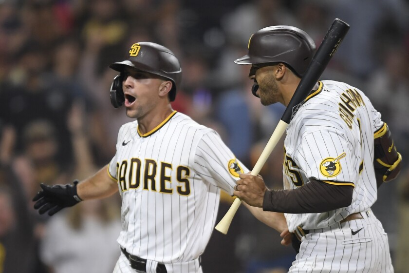 The Padres' Adam Frazier celebrates as he scores next to Trent Grisham