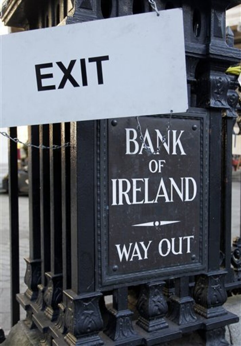 In this photo taken on Nov. 25 2010 an exit sign hangs beside a sign from the Bank of Ireland at one of its branches in Central Dublin, Ireland.  Senior bonds of Allied Irish Banks and Bank of Ireland slumped Friday, Nov. 26, 2010,  amid concern the government will force holders of such debt to sha