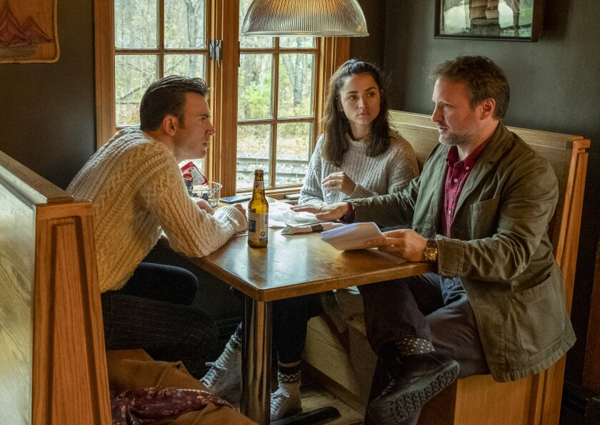 "Chris Evans, left, Ana de Armas and director Rian Johnson on the set of ""Knives Out."""