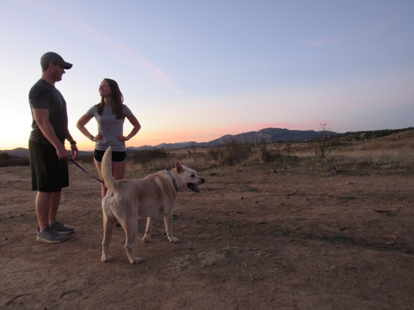 Alpine residents Chris Eaton (left), his wife, Lauren, and their dog, Journey, talk on land slated for a county park.