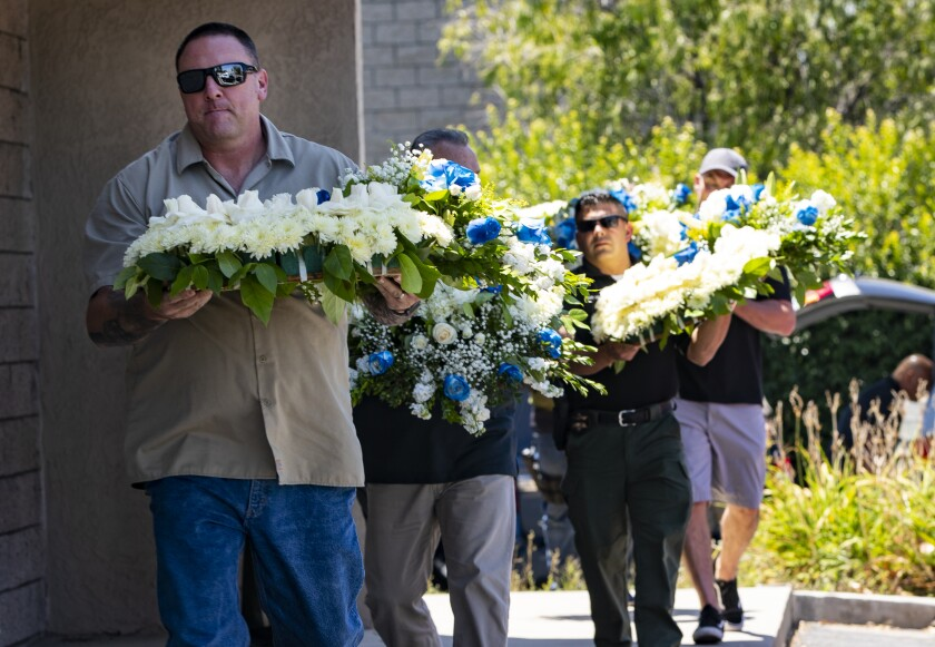 CHP officers and Riverside County deputies carry flowers to be placed in front of the CHP station in Riverside in memory of fallen Officer Andre Moye.