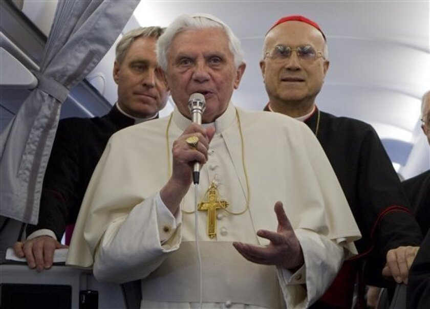 Pope Benedict XVI, flanked by his secretary Georg Gaenswein, left, and Vatican secretary of state Cardinal Tarcisio Bertone, talks to journalist on an aircraft on his way to Malta, Saturday, April 17, 2010. The pope is scheduled meet with the president and visit a grotto linked to St. Paul. On Sund