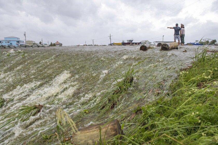 Dos personas miran el agua de mar que superó un dique en el distrito de Plaquemines, al sur de Nueva Orleans, mientras el huracán Barry tocaba tierra en la costa.