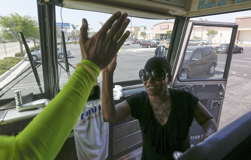 Artist David Gleeson high-fives a woman who came by his Trump bus, parked in a Wal-Mart parking lot in Torrance to volunteer her support, until she found out that the bus was an anti-Trump statement.