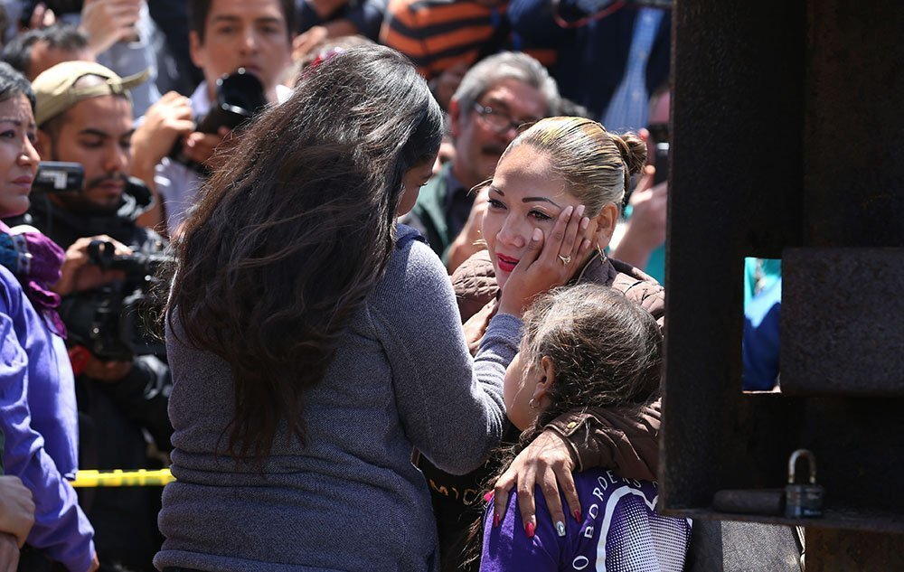 Isela Michel Zavala wipes a tear from her mother Yudridia Guadalupe Zavala, whose arm is draped over Isela's daughter Briana Montes, as they meet in the Door of Hope at Borderfield State Park Saturday.