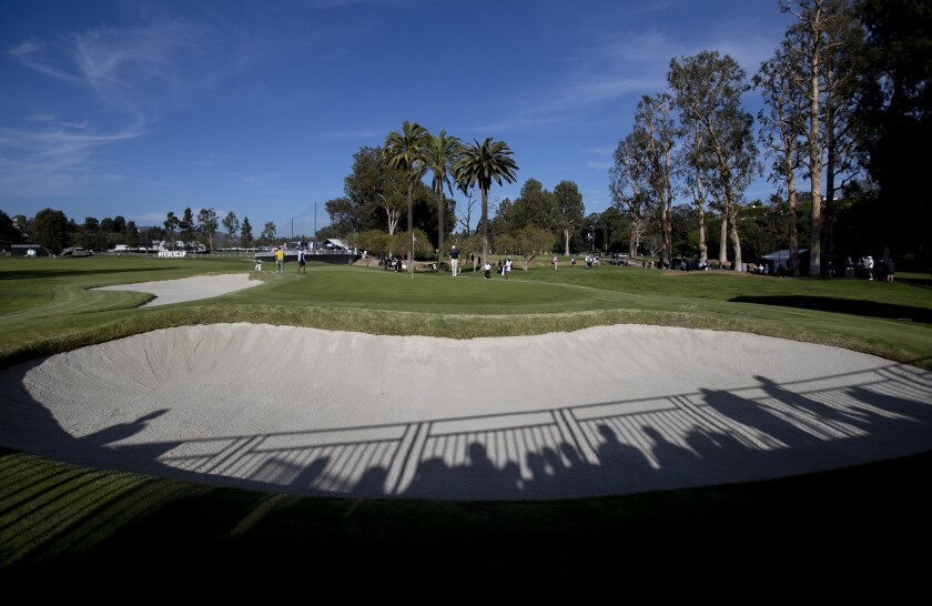 Shadows of the gallery fall into one of the many sand traps surrounding the 10th hole during Round 1 of the Genesis Invitational at Riviera Country Club.