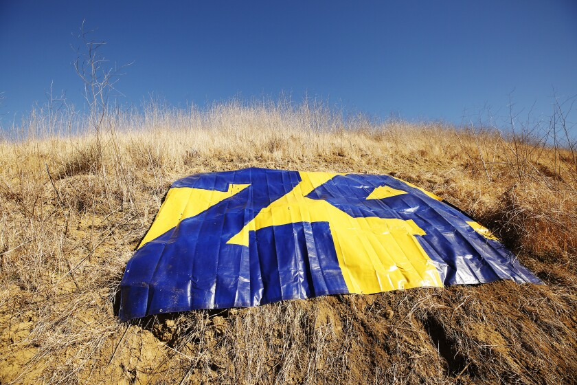 A tarp painted with Kobe Bryant's No. 24 where a helicopter crashed one year ago killing Bryant and eight others.