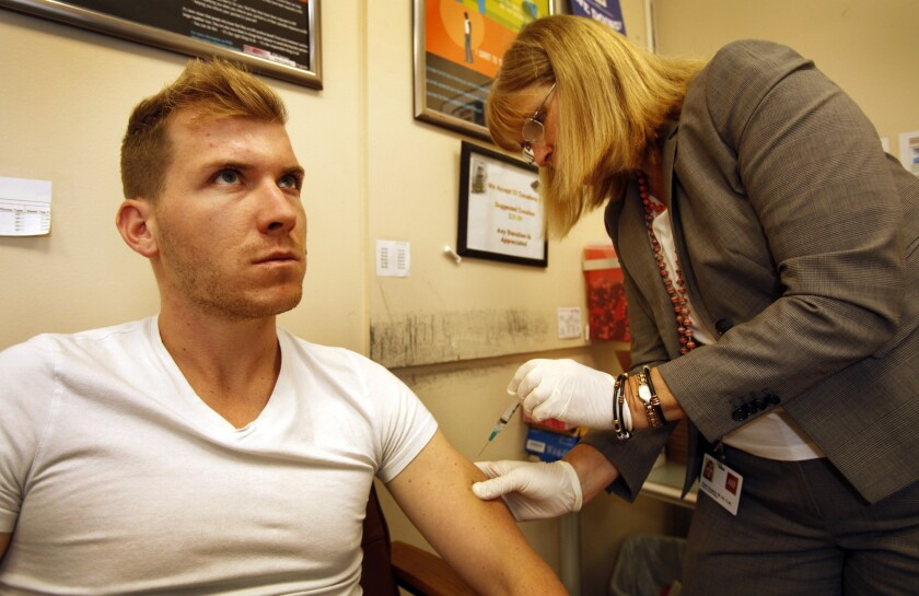 Dylan Cantrell, 27, from West Hollywood focuses as nurse Karen Haughey administers his meningitis vaccination.