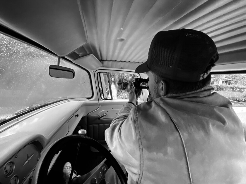 Photographer Brian Bowen Smith sits at the steering wheel of his Ford truck and shoots a portrait through the window.