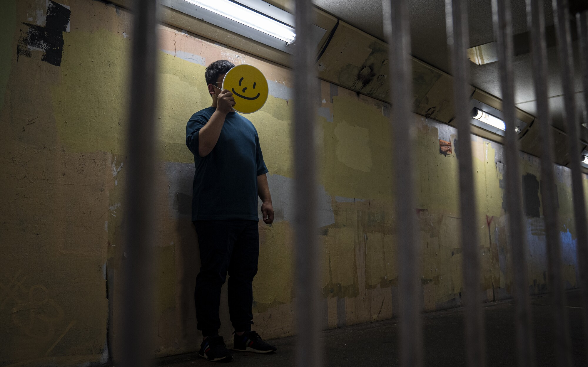 A man holds a yellow smiley face sign in front of his face in a dimly lit hallway, seen through metal bars