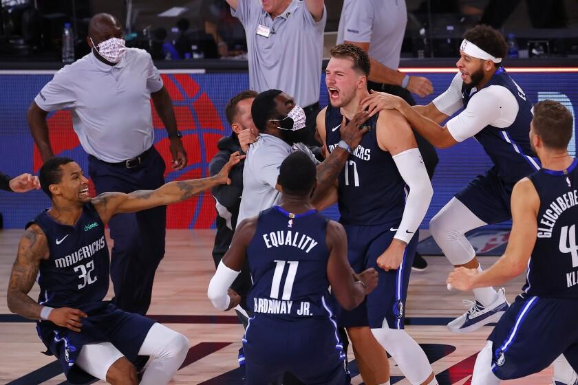 Dallas Mavericks' Luka Doncic celebrates his winning three-point basket with teammates.