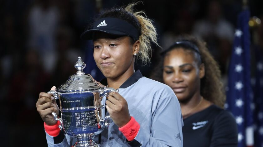 Naomi Osaka, of Japan, holds the trophy after defeating Serena Williams in the women's final of the