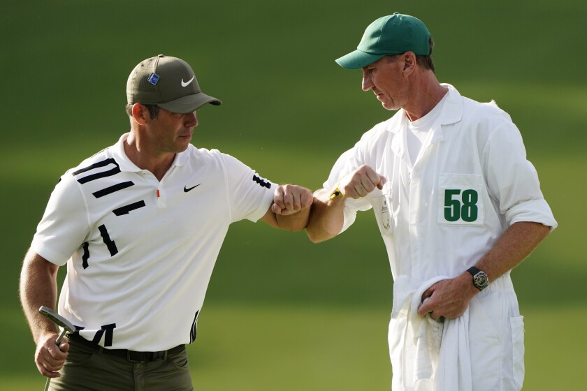 Paul Casey, of England, touches elbows with his caddie John MacLaren after his first round of the Masters golf tournament Thursday, Nov. 12, 2020, in Augusta, Ga. (AP Photo/Matt Slocum)