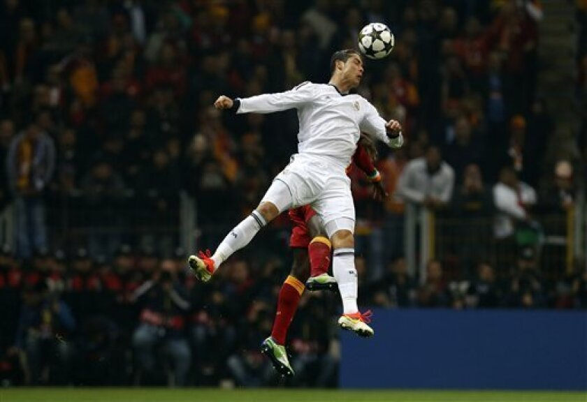 Real Madrid's Ronaldo fights for the ball with Galatasaray's unidentified player during a Champions League quarterfinal soccer match at Ali Sami Yen Spor Kompleksi in Istanbul, Turkey, Tuesday, April 9, 2013. (AP Photo/Thanassis Stavrakis)