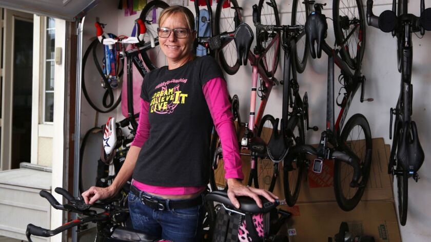 Triathlete Michellie Jones in her garage with a collection of race bicycles.