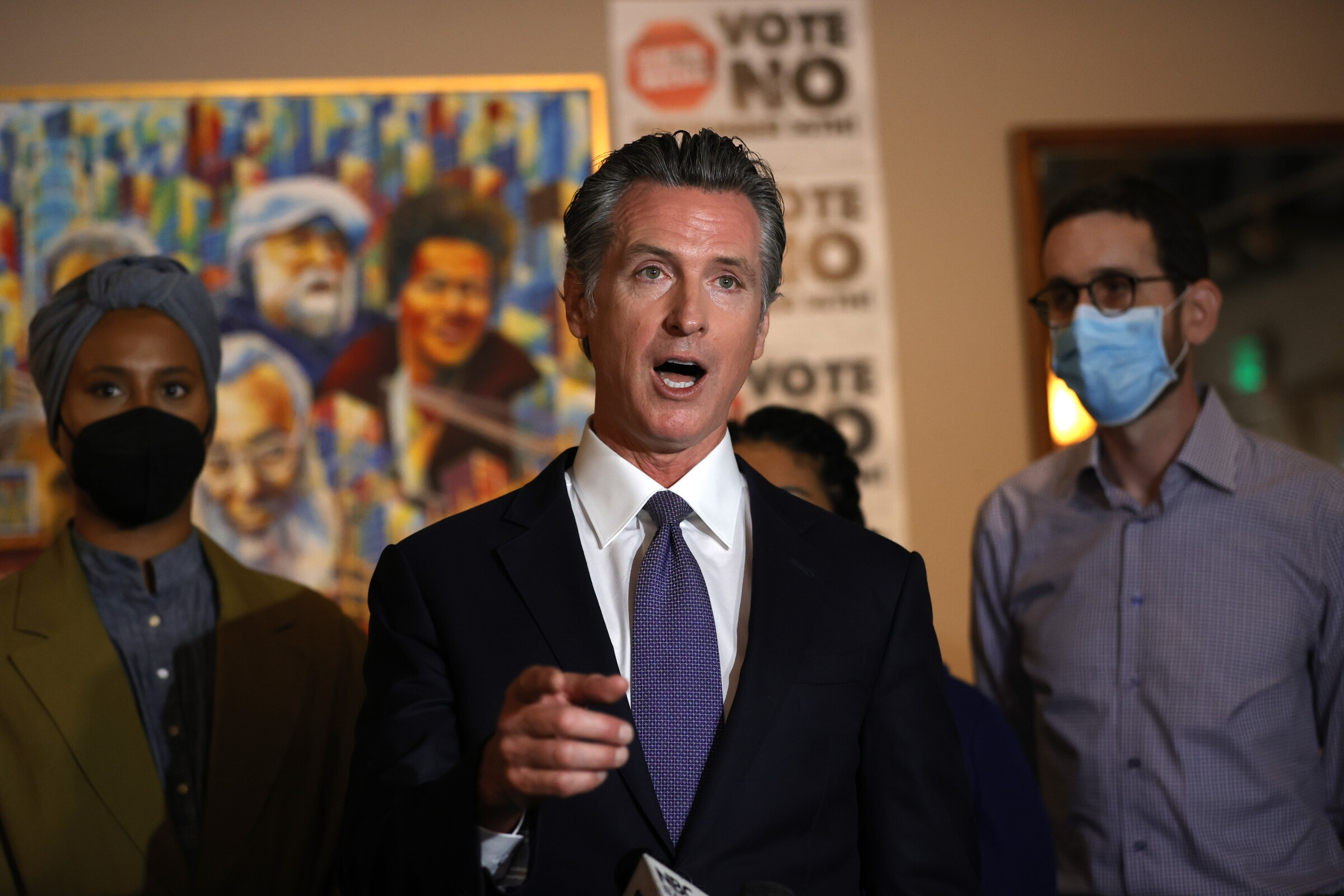 Gavin Newsom, in suit and tie with two people in masks behind him, speaks to media.