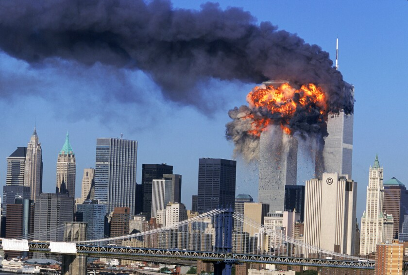 An explosion rips through the south tower of the World Trade Center as smoke billows from the north tower.