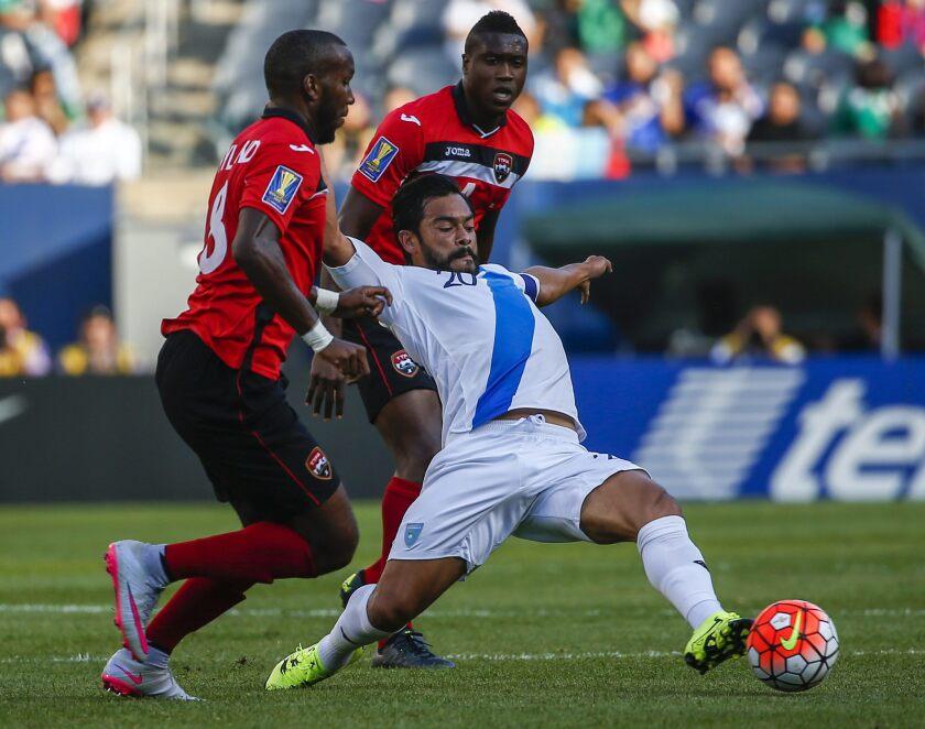 El jugador de la selección nacional de fútbol de Trinidad y Tobago Khaleem Hyland (i) y Sheldon Bateau (d) disputan el balón con Carlos Ruiz (c) de Guatemala.