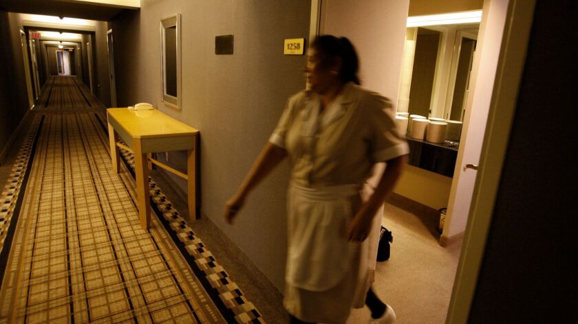 Maria Jimenez, a housekeeper, closes a door on the 12th floor of the Wilshire Grand Hotel.