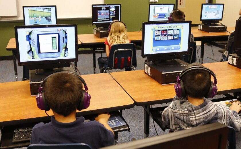 Students use computers and headphones for academic lessons. Vista Unified School district is considering reducing some technology costs, to cut $13.3 million from next year's 2020-21 budget.