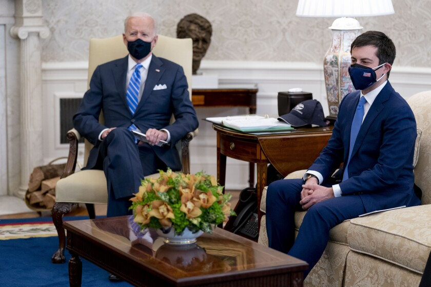 President Biden sits on a chair and Pete Buttigieg sits on a sofa in the Oval Office