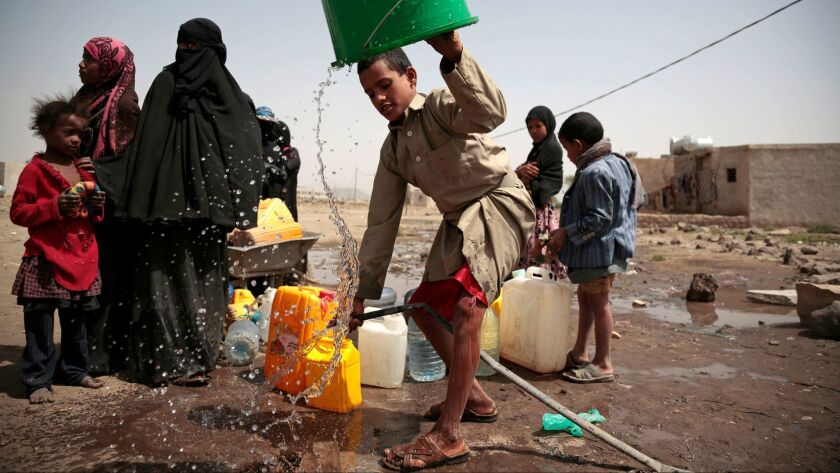 A boy rinses a bucket as he and others collect water from a well believed to be contaminated with cholera bacteria on the outskirts of Sana in Yemen on July 12, 2017.