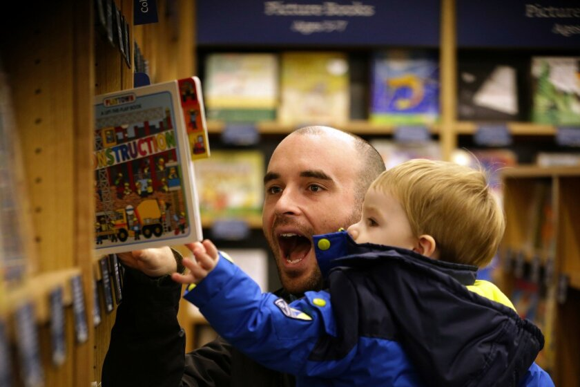 Customer Michael Wallenfels looks at children's books with his son Henry, 2, at the opening day for Amazon Books, the first brick-and-mortar retail store for online retail giant Amazon, Tuesday, Nov. 3, 2015, in Seattle.