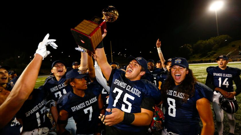 Oceanside's Isaiah Kaleopa-Tuise'e hoists the winner's trophy in the air for the North team after their 23-17 victory.