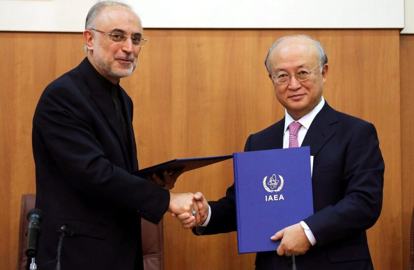 The head of Iran's Atomic Energy Organization, Ali Akbar Salehi, shakes hands with International Atomic Energy Agency chief Yukiya Amano, right, after signing an agreement in Tehran to allow inspectors broader access to Iranian nuclear sites.
