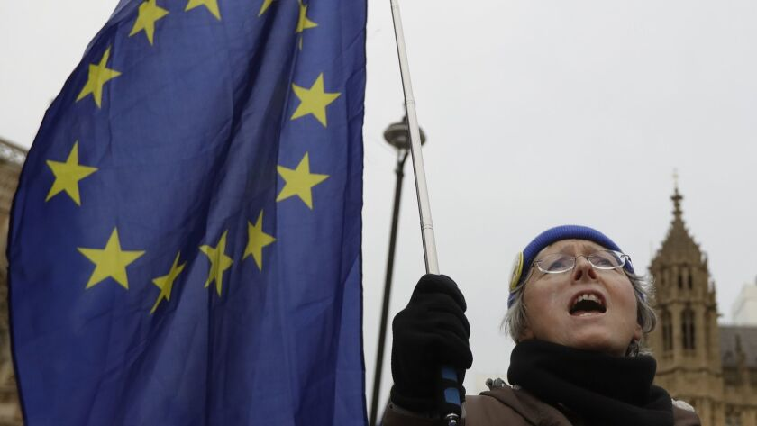 An Anti Brexit campaigner waves a European Union flag in Westminster in London, Tuesday, Dec. 4, 201