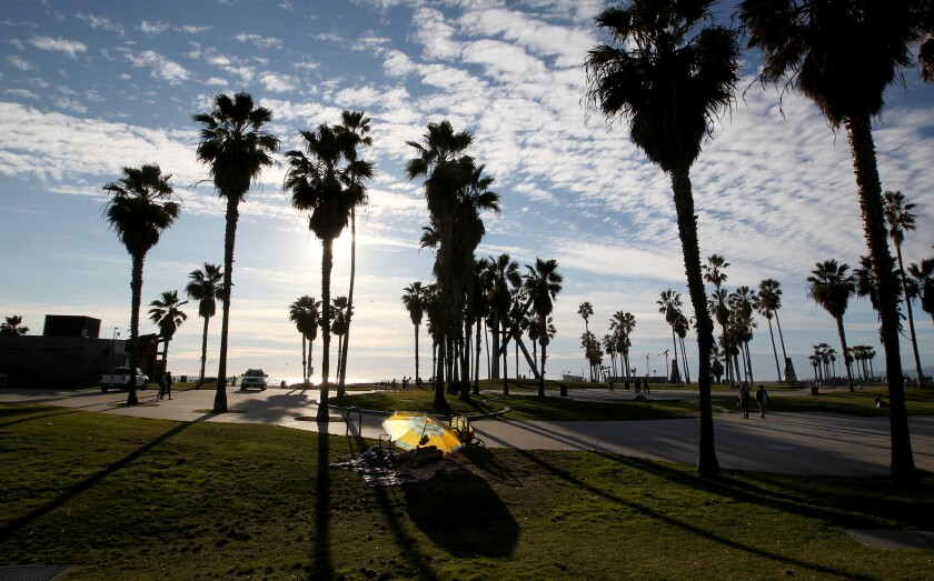 A homeless person huddles under blankets in Venice Beach, which is part of District 11.