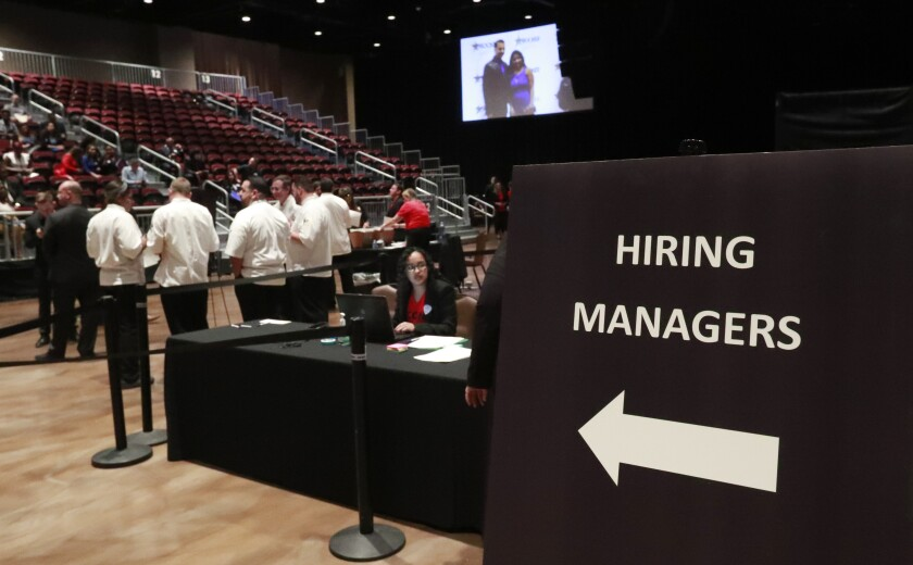 FILE - In this Tuesday, June 4, 2019, file photo, managers wait for job applicants at the Seminole Hard Rock Hotel & Casino Hollywood during a job fair in Hollywood, Fla. U.S. businesses added 183,000 jobs in Jan. 2020, a solid gain that shows the economy was largely healthy when the coronavirus outbreak spread further around the globe. Large companies added roughly two-thirds of the jobs, while hiring among smaller firms was relatively weak. Manufacturing and mining firms shed jobs, while hiring in health care and hotels and restaurants was strong. (AP Photo/Wilfredo Lee, File)