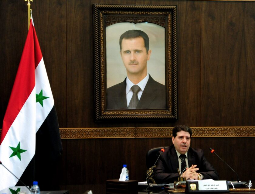 Syrian Prime Minister Wael Halqi leading the weekly Ministers Council meeting in Damascus. New U.S. sanctions target four Syrian government officials.