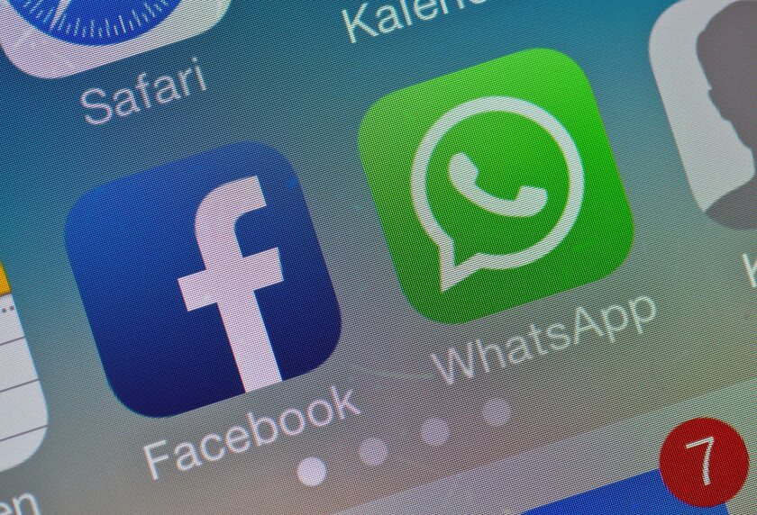 The two logos of Facebook and WhatsApp pictured on the screen of a smartphone.