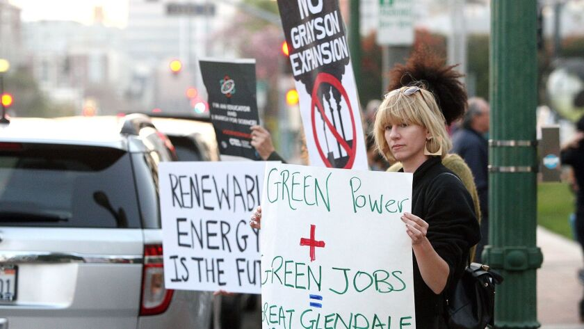 Protesters hold signs for passing motorists at a rally hosted by the Glendale Environmental Coalition to oppose expansion of the Grayson Power Plant, on the steps of Glendale City Hall on Tuesday, Feb. 6, 2018.