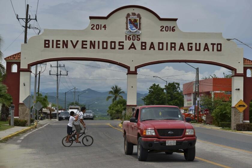 En esta imagen del 20 de julio de 2015, un auto pasa junto a la entrada de Badiraguato, México. Incrustado en las pequeñas colinas donde los tramos costeros de campos de maíz y tomate se unen a las imponentes montañas de la Sierra Madre, Badiraguato sigue sumido en la pobreza.